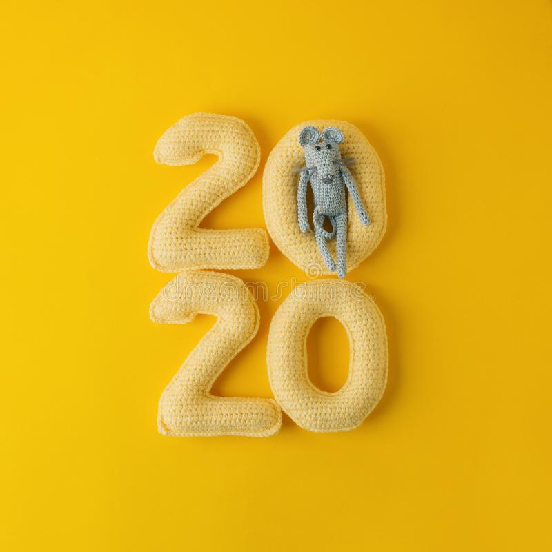 Happy New Year 2020. Number 2020 knitted from yarn and gray toy mouse symbol of year on bright yellow background, cheese color. Fl. At lay, top view, copy space stock images