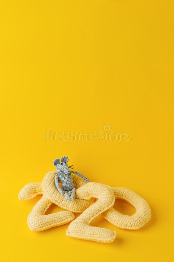 Happy New Year 2020. Number 2020 knitted from yarn and gray toy mouse symbol of year on bright yellow background, cheese color. Fl. At lay, top view, copy space royalty free stock images