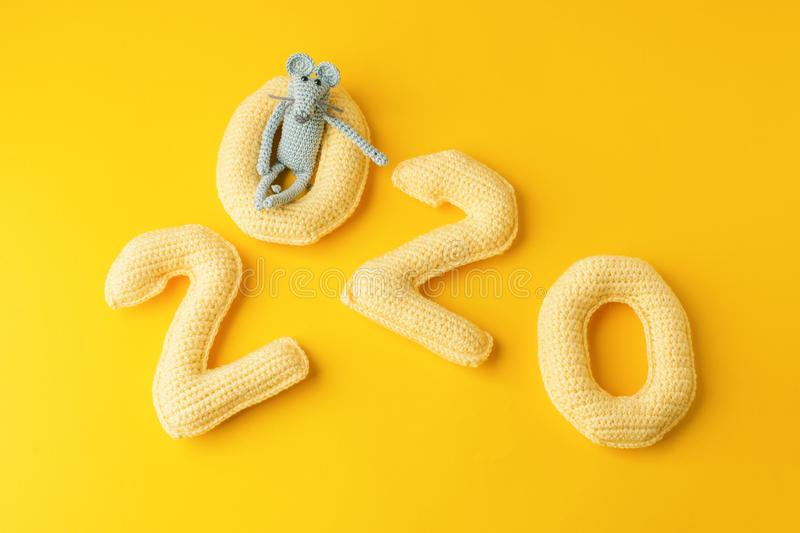 Happy New Year 2020. Number 2020 knitted from yarn and gray toy mouse symbol of year on bright yellow background, cheese color. Flat lay, top view, copy space royalty free stock photo