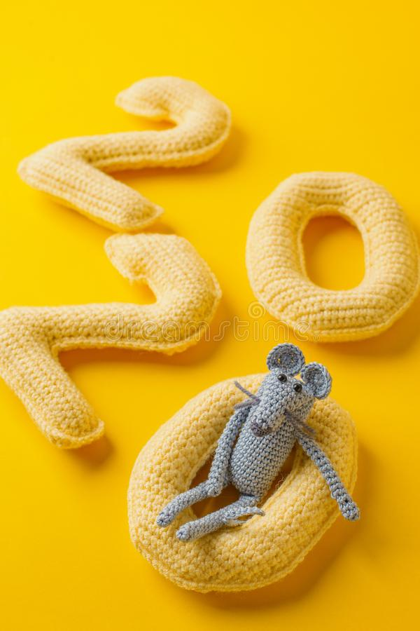 Happy New Year 2020. Number 2020 knitted from yarn and gray toy mouse symbol of year on bright yellow background, cheese color. Flat lay, top view, copy space stock photo