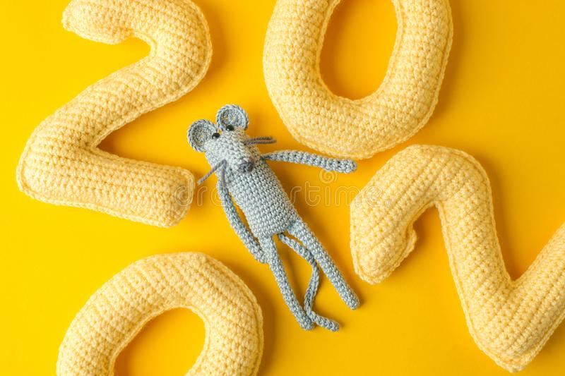 Happy New Year 2020. Number 2020 knitted from yarn and gray toy mouse symbol of year on bright yellow background, cheese color. Flat lay, top view, copy space stock image