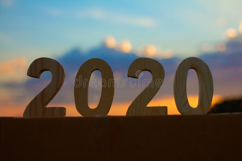 Happy New Year 2020 number on nature blue sky and sunset light, holiday nature concept stock photos