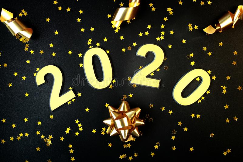 2020 Happy New Year. Number 2020 written on black background. Glowing overlay template for holiday greeting card royalty free stock photo