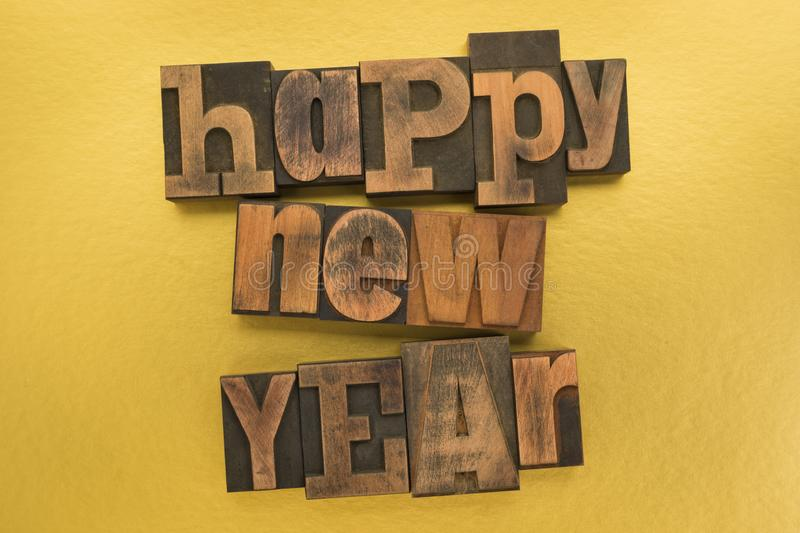 Happy new year written with vintage letterpress printing blocks on gold colored background stock image