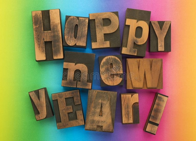 Happy new year written with vintage letterpress printing blocks on rainbow background stock photography