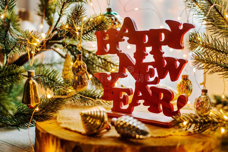 Happy new year. Red happy new year sign on a wooden background with fur tree, lights and vitntage Soviet toys royalty free stock image