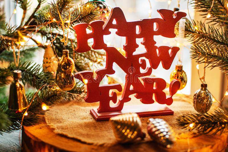 Happy new year. Red happy new year sign on a wooden background with fur tree, lights and vitntage Soviet toys stock images