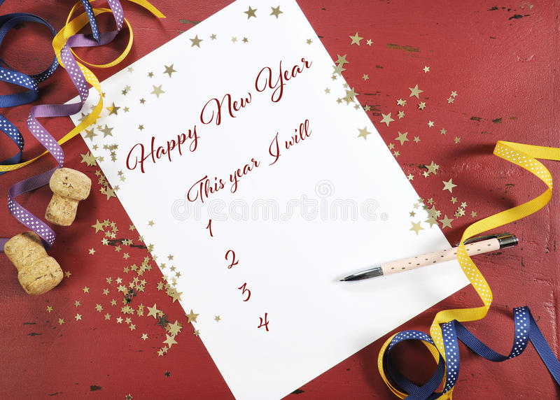 Happy New Year Resolutions planning and goal list. On dark red wood background with gold stars and festive decorations royalty free stock image