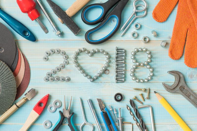Happy new year 2018. RHappy new year 2018 composition with screws, nails, bolts , dowels and tools on blue wooden background. New year. New year background stock image