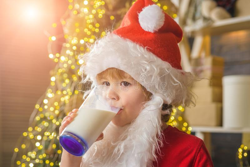 Happy New Year. Santa Claus. Happy kids Santa Claus with glass of milk and cookie. Cheerful little Santa Claus holding. Glass with milk and cookie with royalty free stock images
