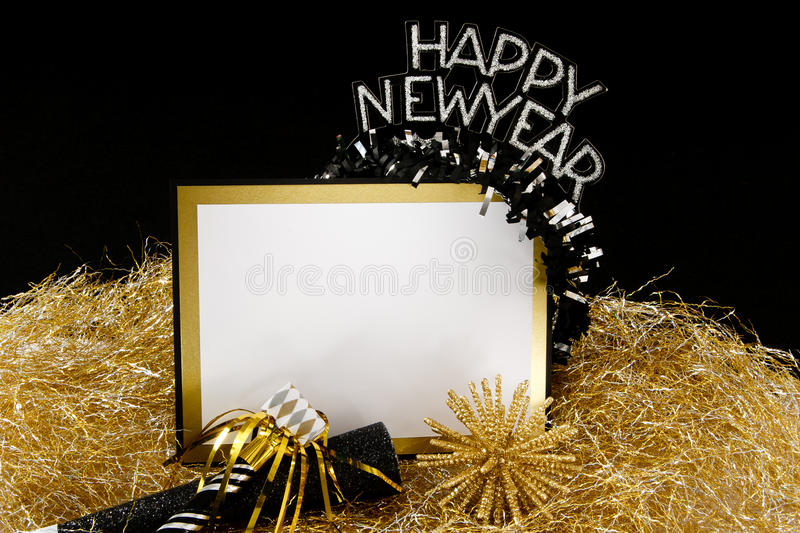 Happy New Year Sign in Black and Gold. Happy New Year sign or invitation with copy-space in black and gold with tradtional party favors stock image