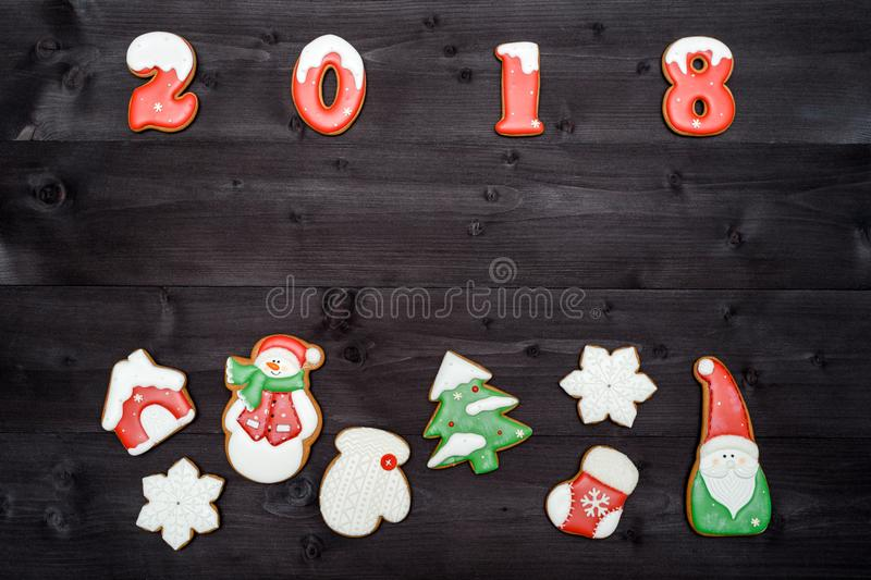 Happy new year 2018 sign symbol from red and white gingerbread cookies on dark wooden background, copy space. Top view, flat lay royalty free stock photo