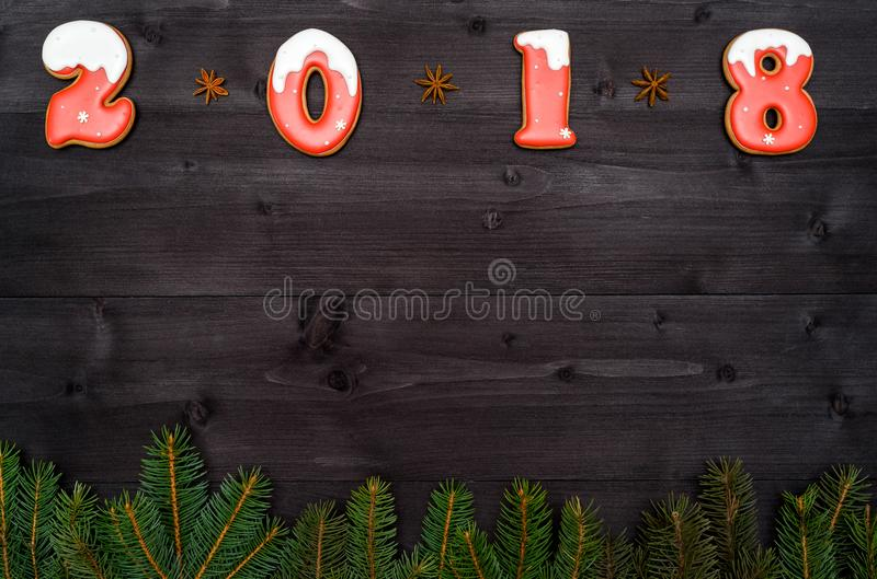 Happy new year 2018 sign symbol from red and white gingerbread cookies on dark wooden background with fir tree branches. royalty free stock images