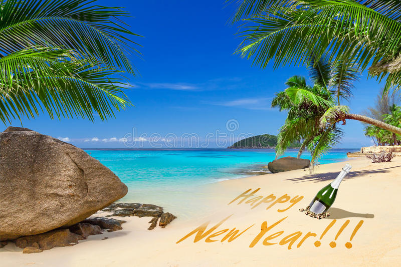 Happy New Year sign on the tropical beach. With champagne royalty free stock photo