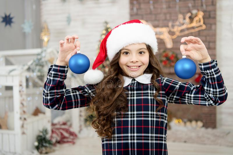 Happy new year. smiling child in santa hat. winter holiday activity. christmas shopping. small girl elf costume. trendy. Kid decorative xmas ball. home and stock photo
