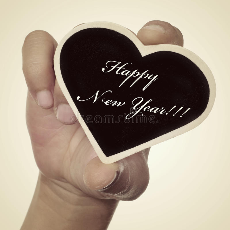 Happy new year. Someone showing a small heart-shaped blackboard with the sentence happy new year written in it, with a retro effect stock photos