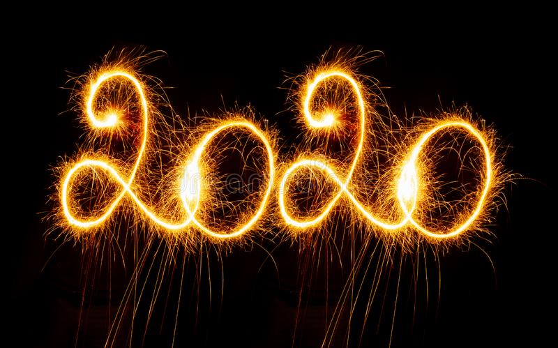 Happy New Year - 2020 with sparklers on black background stock image