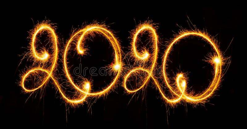 Happy New Year - 2020 with sparklers on black background. Happy New Year 2020 with sparklers on black background royalty free stock image