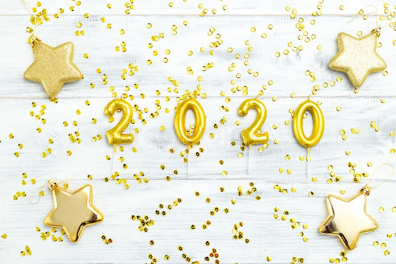 Happy New Year 2020. Symbol from golden number 2020 and golden sparkle on white wooden background. Flat lay royalty free stock photo