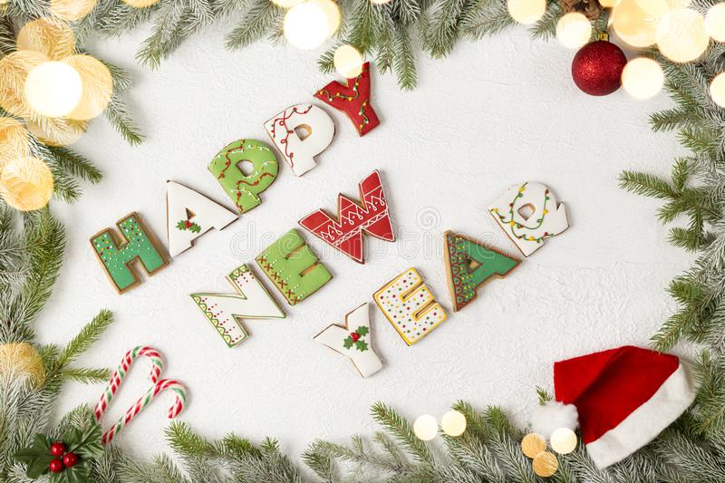 Happy New Year. Table top shot of gingerbread cookies shaped as letters Happy New Year in a frame made of fir branches and christmas lights royalty free stock photos