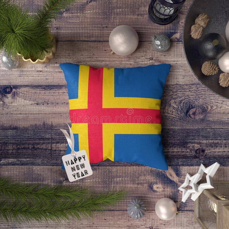 Happy New Year tag with Aland Island flag on pillow. Christmas decoration concept on wooden table with lovely objects.  stock photo