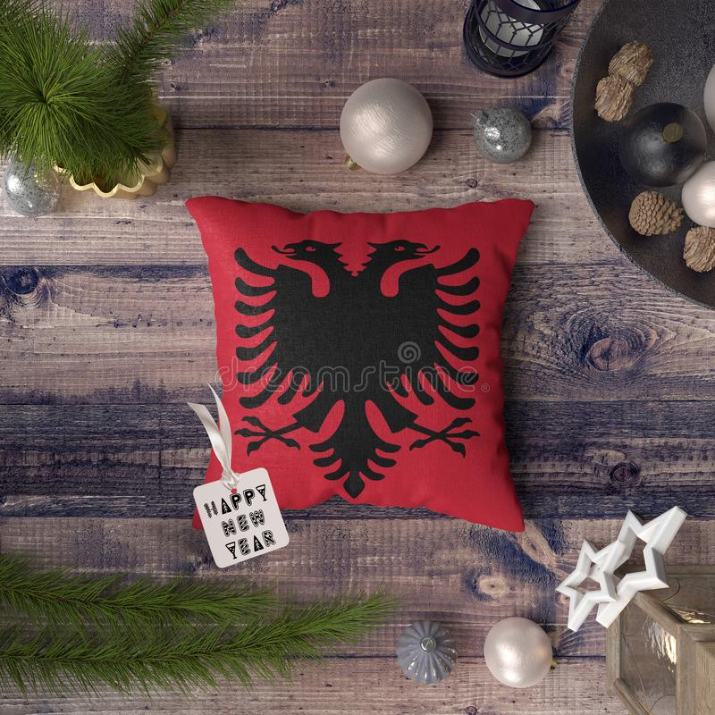 Happy New Year tag with Albania flag on pillow. Christmas decoration concept on wooden table with lovely objects.  royalty free stock photo