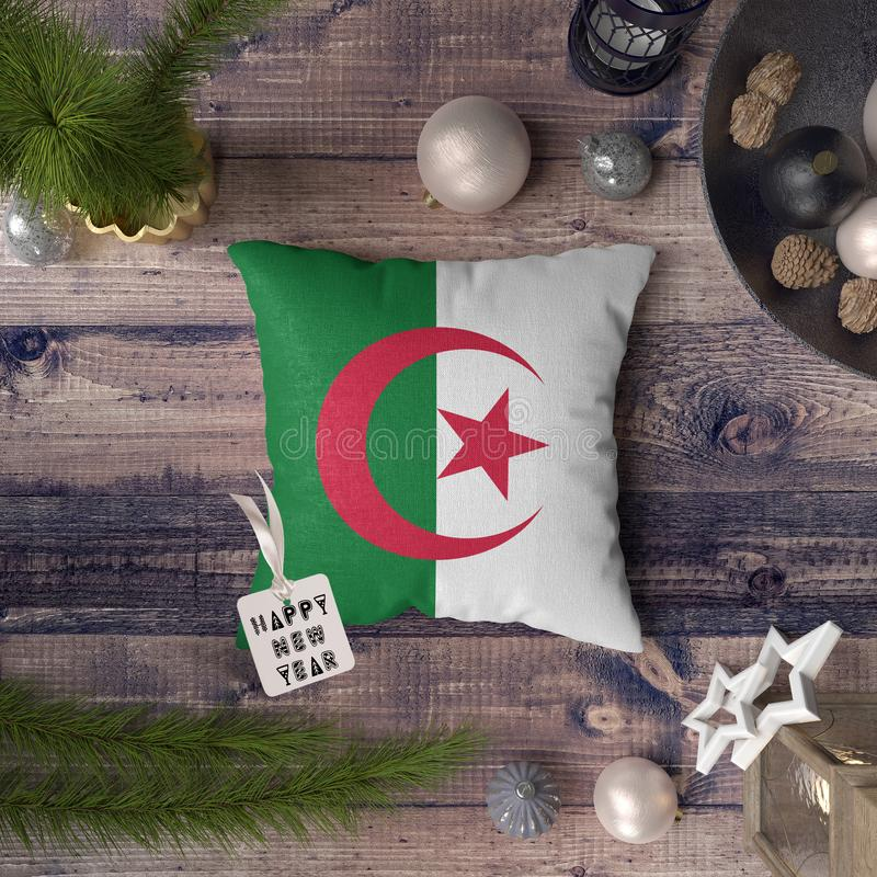 Happy New Year tag with Algeria flag on pillow. Christmas decoration concept on wooden table with lovely objects.  stock photography