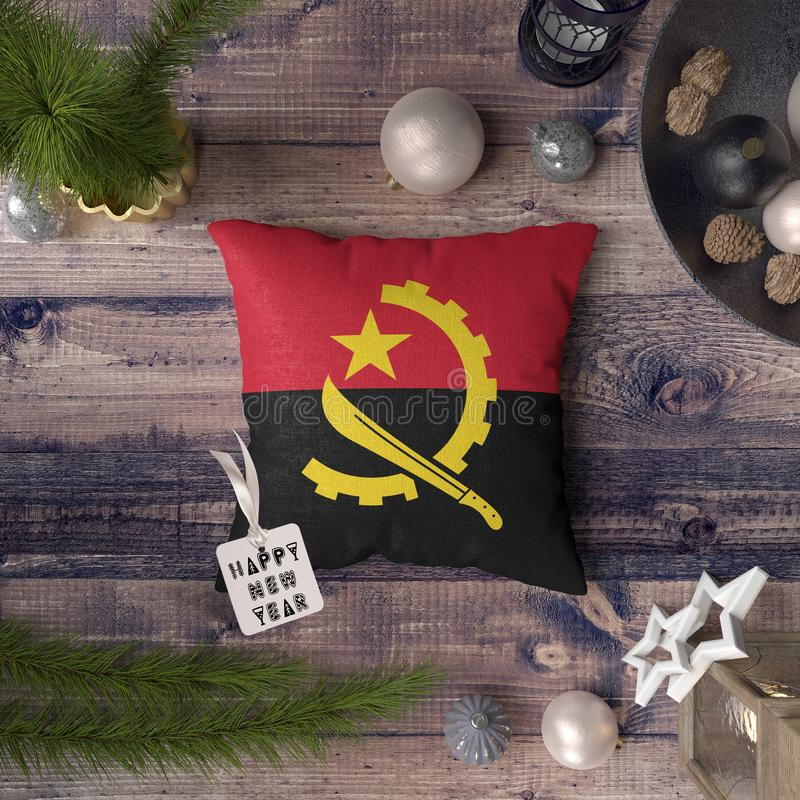 Happy New Year tag with Angola flag on pillow. Christmas decoration concept on wooden table with lovely objects.  stock image