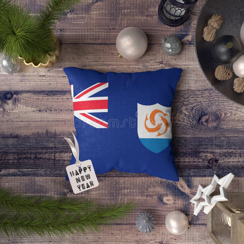 Happy New Year tag with Anguilla flag on pillow. Christmas decoration concept on wooden table with lovely objects.  royalty free stock image