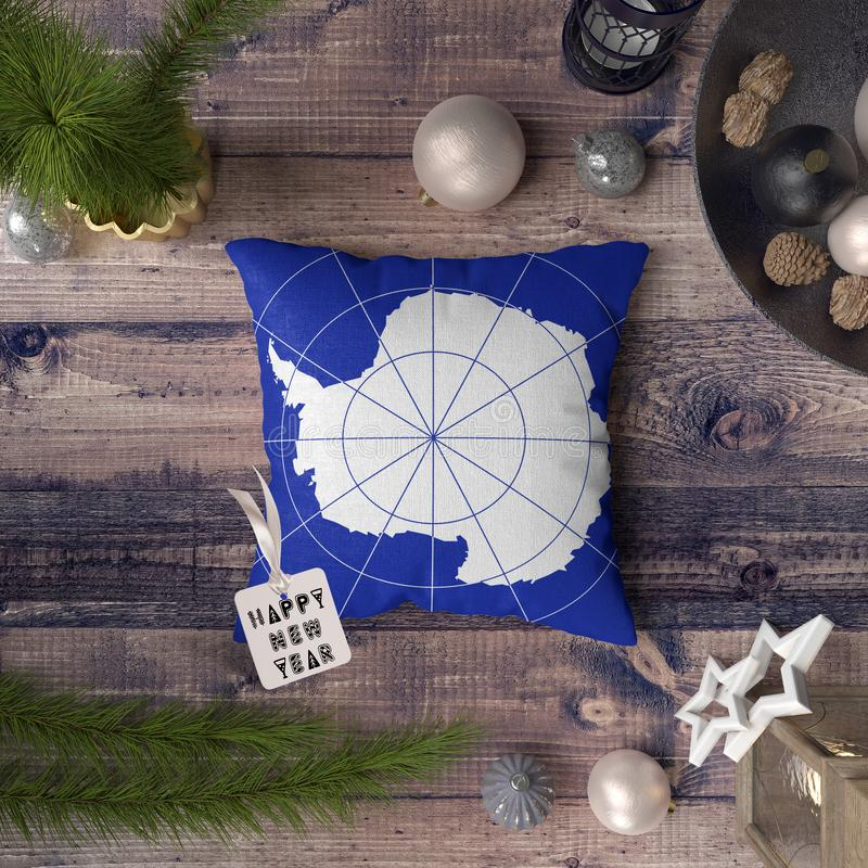 Happy New Year tag with Antarctica flag on pillow. Christmas decoration concept on wooden table with lovely objects.  royalty free stock photo