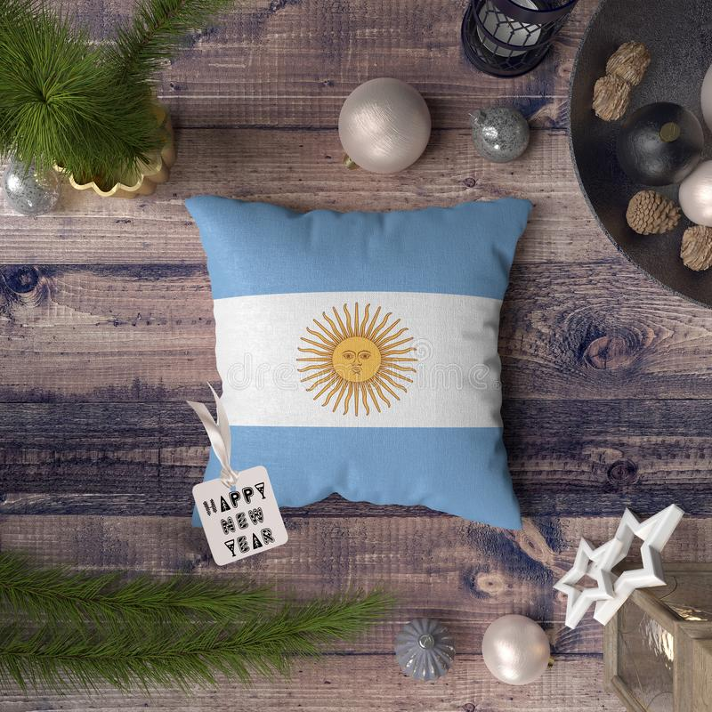 Happy New Year tag with Argentina flag on pillow. Christmas decoration concept on wooden table with lovely objects.  stock photos