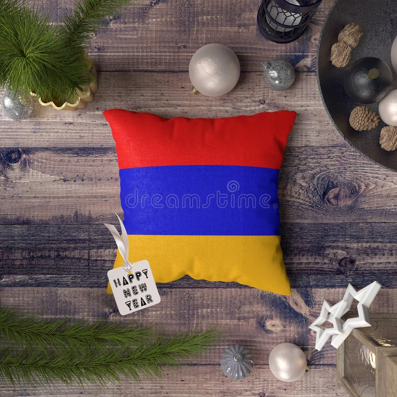 Happy New Year tag with Armenia flag on pillow. Christmas decoration concept on wooden table with lovely objects.  stock images