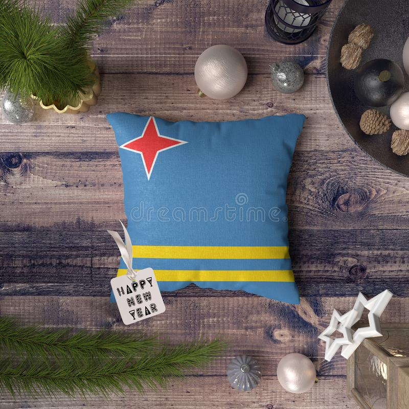 Happy New Year tag with Aruba flag on pillow. Christmas decoration concept on wooden table with lovely objects.  royalty free stock photos