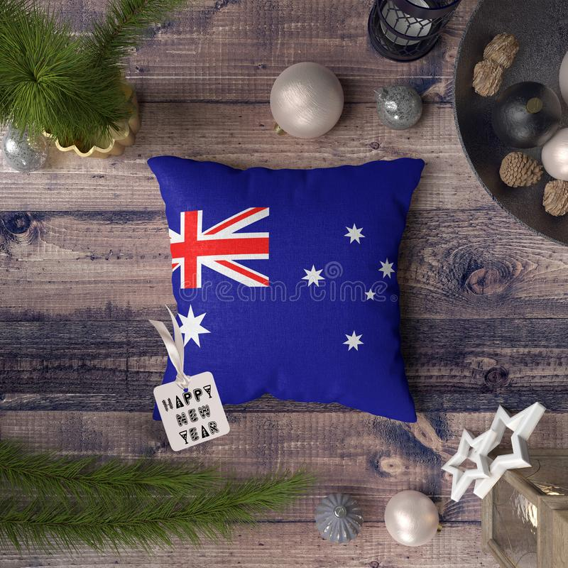 Happy New Year tag with Australia flag on pillow. Christmas decoration concept on wooden table with lovely objects.  royalty free stock photo