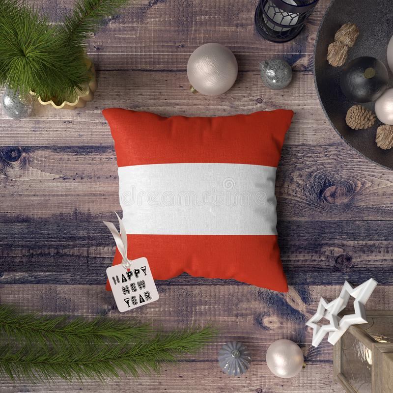 Happy New Year tag with Austria flag on pillow. Christmas decoration concept on wooden table with lovely objects.  royalty free stock photo