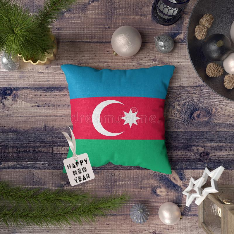 Happy New Year tag with Azerbaijan flag on pillow. Christmas decoration concept on wooden table with lovely objects.  royalty free stock images