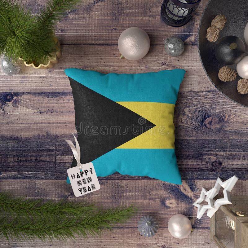 Happy New Year tag with Bahamas flag on pillow. Christmas decoration concept on wooden table with lovely objects.  stock photos