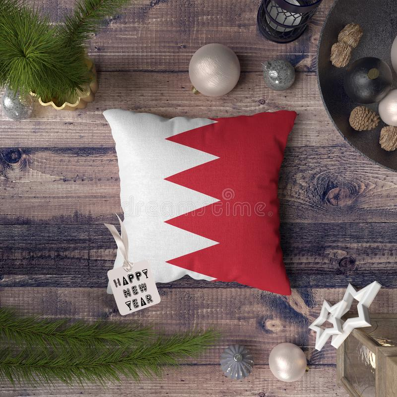 Happy New Year tag with Bahrain flag on pillow. Christmas decoration concept on wooden table with lovely objects.  royalty free stock photo