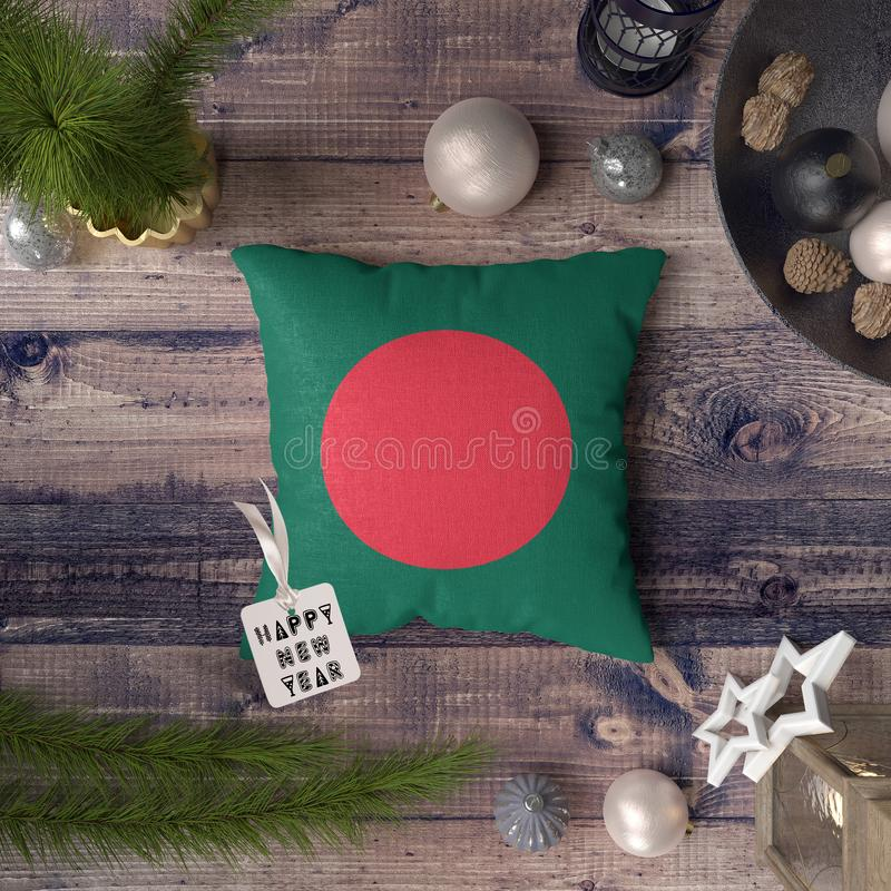 Happy New Year tag with Bangladesh flag on pillow. Christmas decoration concept on wooden table with lovely objects.  stock image