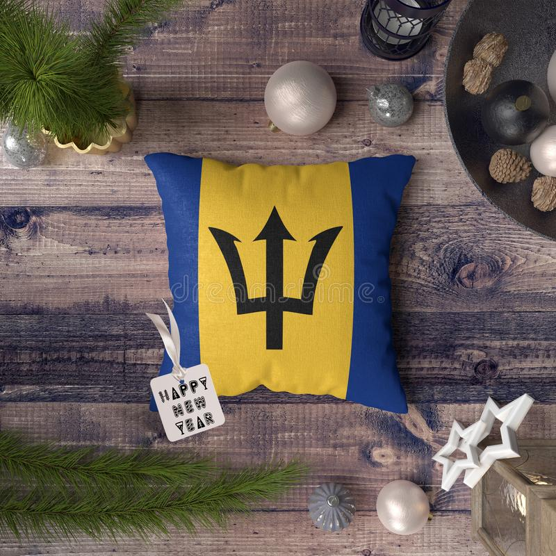 Happy New Year tag with Barbados flag on pillow. Christmas decoration concept on wooden table with lovely objects.  stock photos