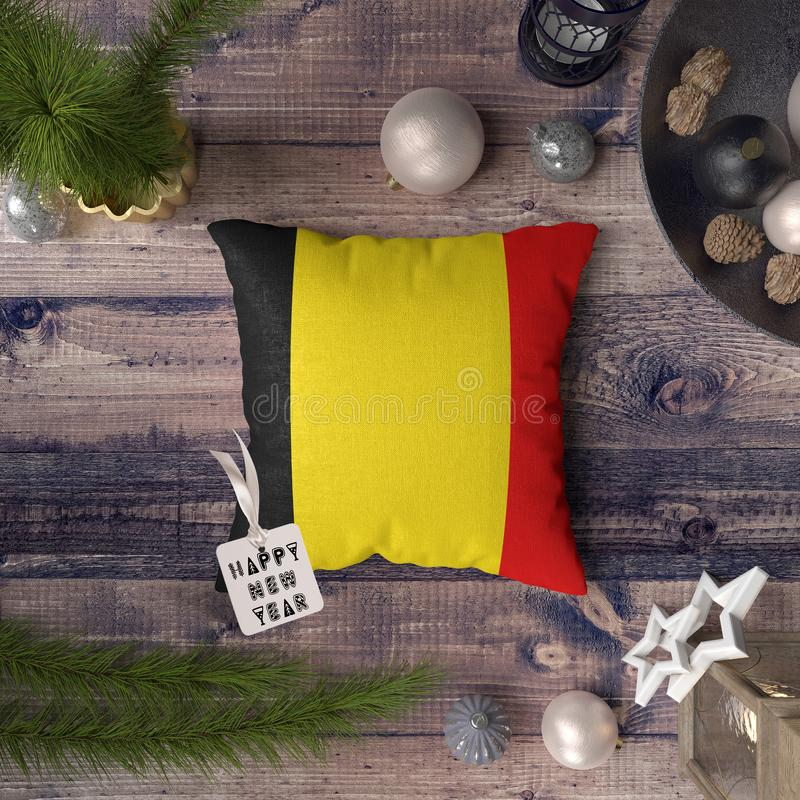 Happy New Year tag with Belgium flag on pillow. Christmas decoration concept on wooden table with lovely objects.  stock photo
