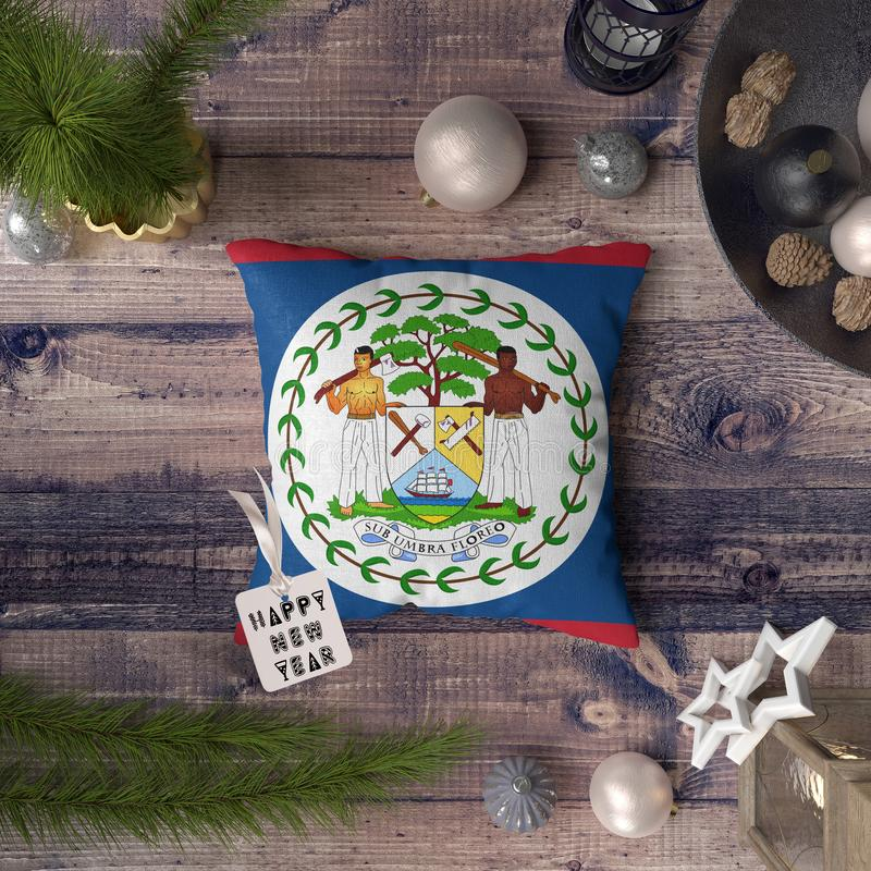 Happy New Year tag with Belize flag on pillow. Christmas decoration concept on wooden table with lovely objects.  royalty free stock photography