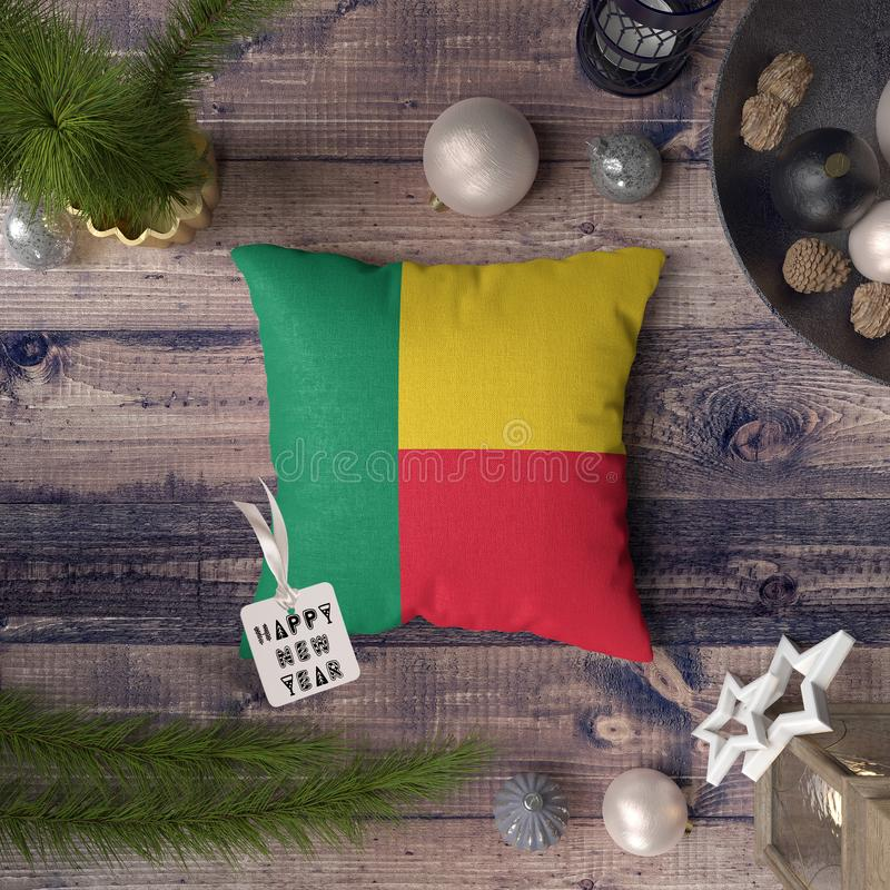 Happy New Year tag with Benin flag on pillow. Christmas decoration concept on wooden table with lovely objects.  stock image