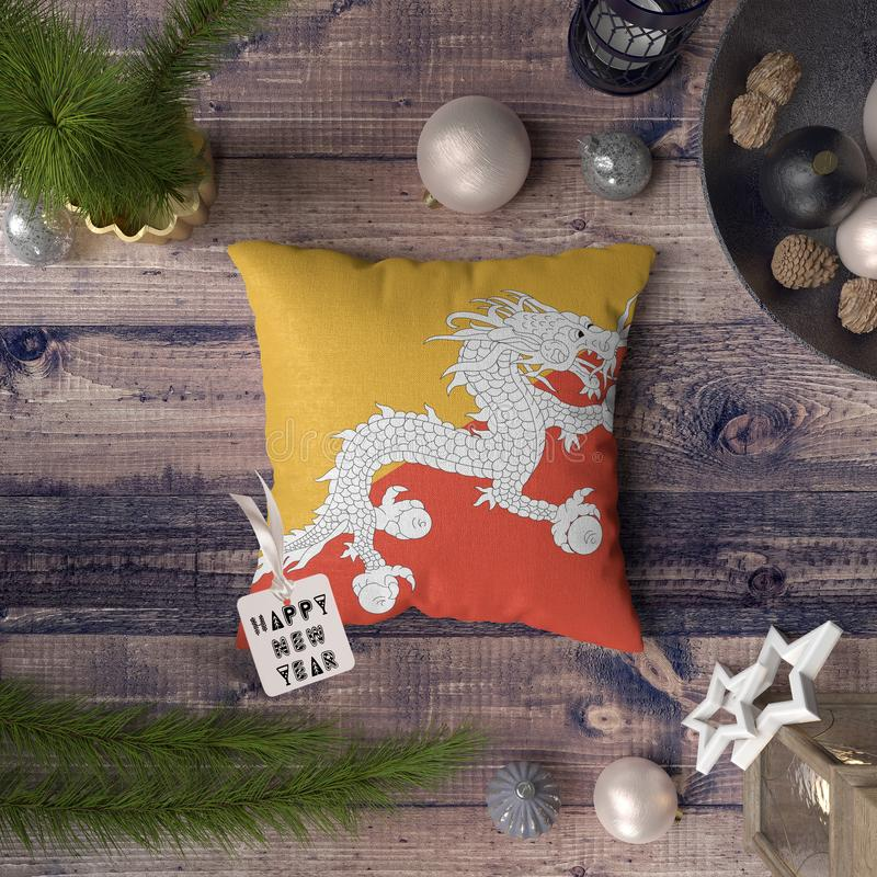 Happy New Year tag with Bhutan flag on pillow. Christmas decoration concept on wooden table with lovely objects.  stock image
