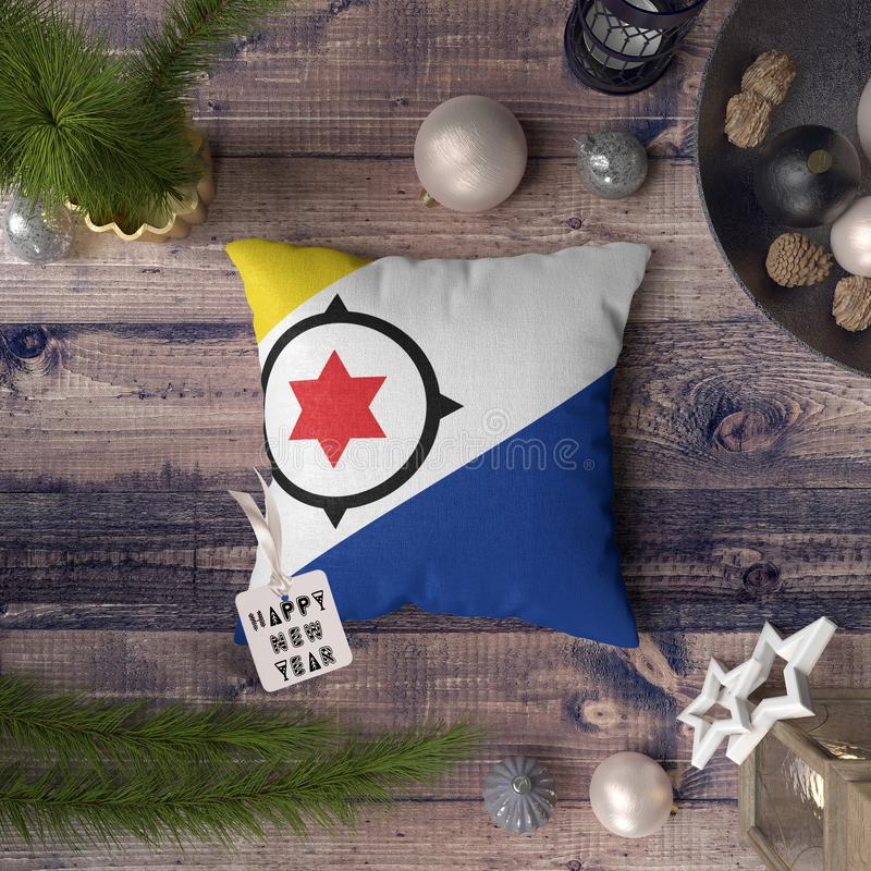 Happy New Year tag with Bonaire flag on pillow. Christmas decoration concept on wooden table with lovely objects.  stock photo