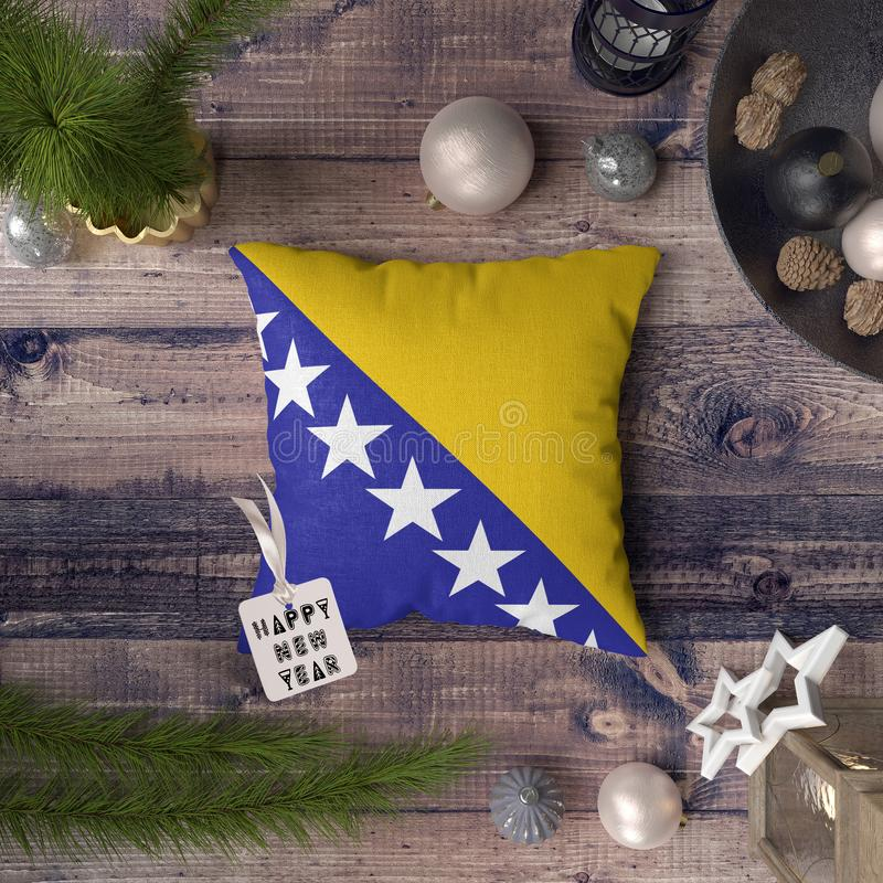 Happy New Year tag with Bosnia Herzegovina flag on pillow. Christmas decoration concept on wooden table with lovely objects.  royalty free stock images
