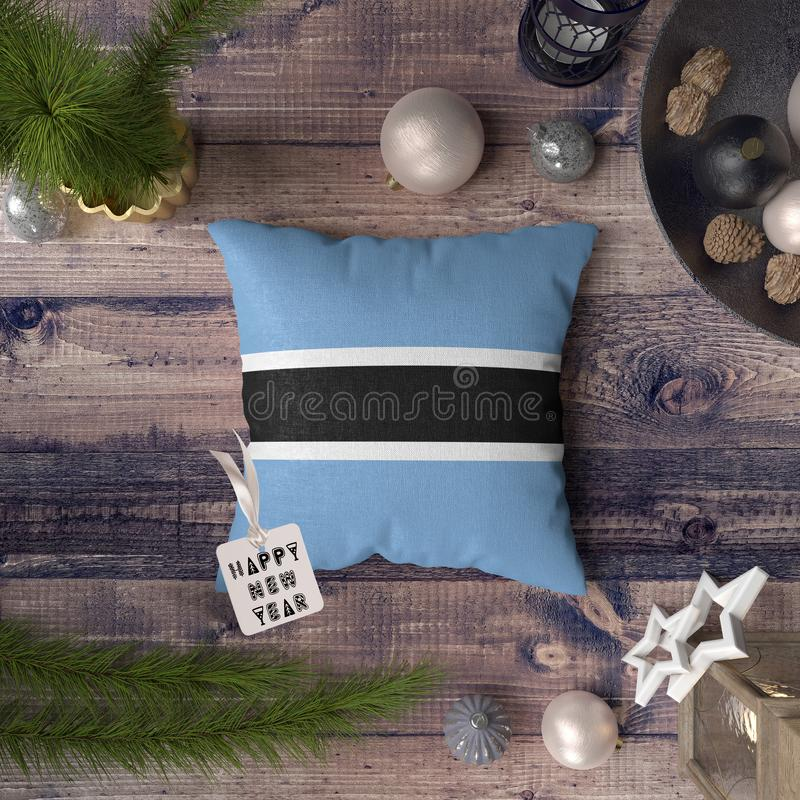 Happy New Year tag with Botswana flag on pillow. Christmas decoration concept on wooden table with lovely objects.  stock photography
