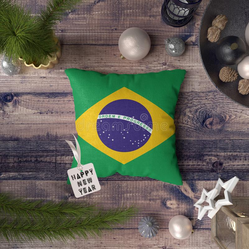 Happy New Year tag with Brazil flag on pillow. Christmas decoration concept on wooden table with lovely objects.  royalty free stock photo