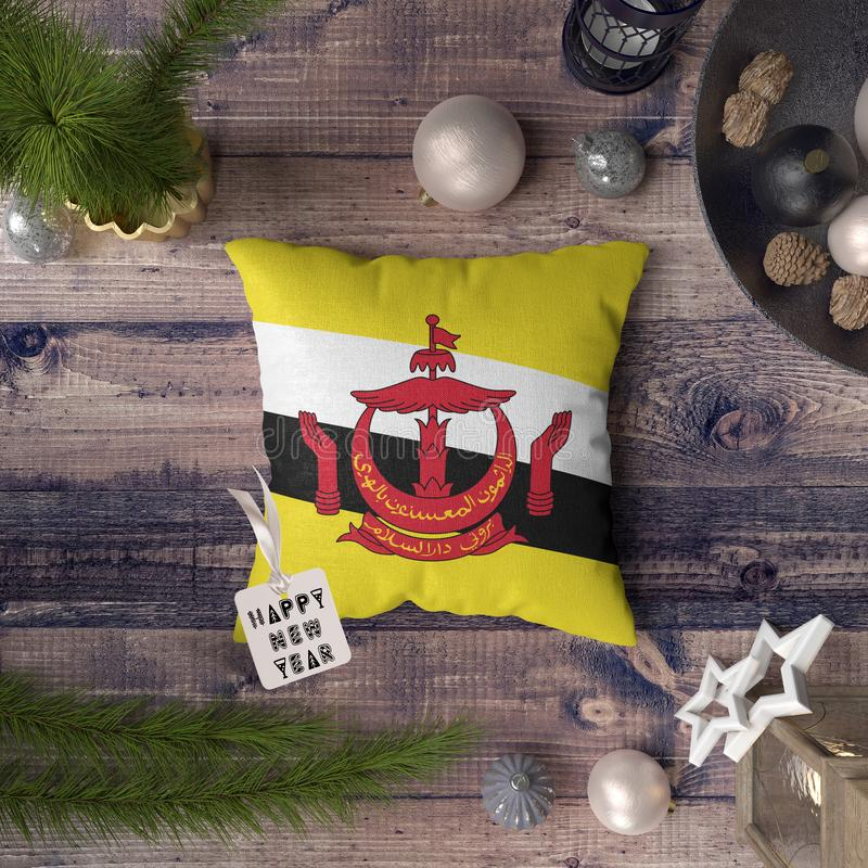 Happy New Year tag with Brunei flag on pillow. Christmas decoration concept on wooden table with lovely objects.  stock image