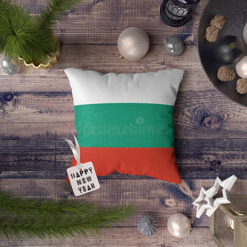 Happy New Year tag with Bulgaria flag on pillow. Christmas decoration concept on wooden table with lovely objects.  stock photo